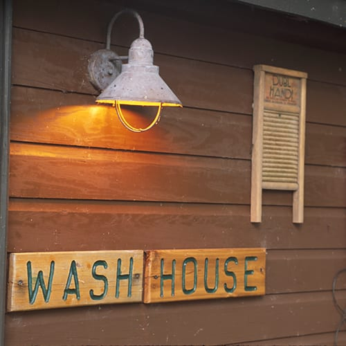 Wash house exterior sign with mounted washboard.