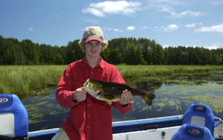 Young man on lake holding a bass.